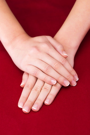 red hand: Beautiful Female Hands on red background french manicure Stock Photo