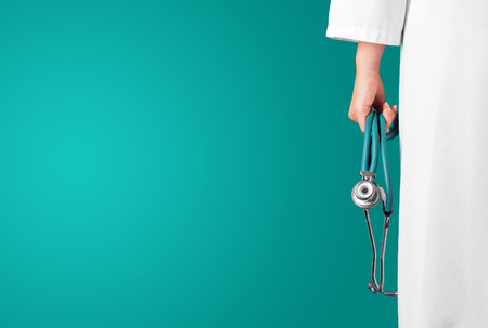 Green medical background with female doctor and stethoscope Stock Photo