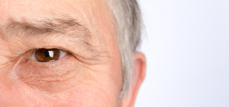 sad eyes: Close-up view on the eye of senior man. Horizontal photo