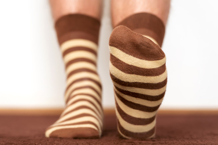 step by step: Wearing comfortable striped socks at home.
