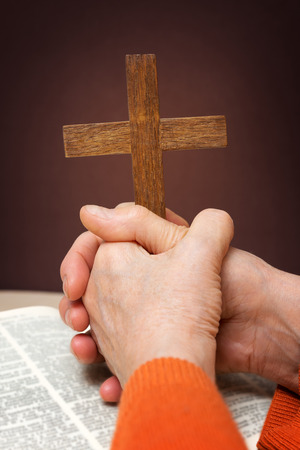 ascetic: Closeup of wooden Christian cross and hand next on holy Bible