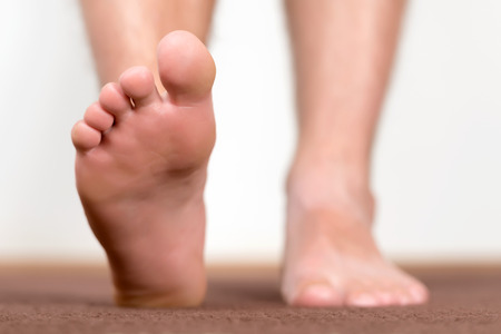 homelike: Healthy male feet stepping over home-like background.