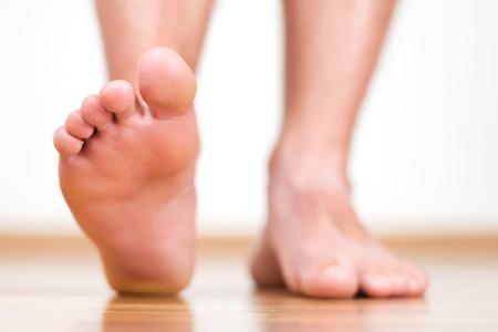 homelike: Healthy male feet stepping over home-like background Stock Photo