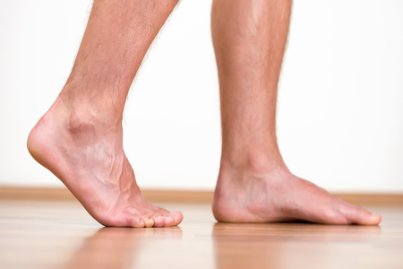barefoot man: Pair of clean male feet without any illness making a step.