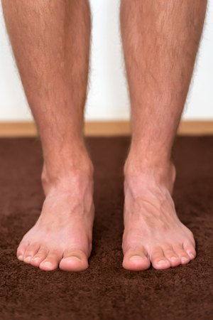 podiatry: Healthy male feet feeling comfortable at home. Stock Photo