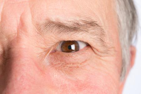 and the horizontal man: Close-up view on the eye of senior man. Horizontal photo