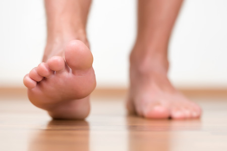 tiptoe: Healthy male feet stepping over home-like background Stock Photo