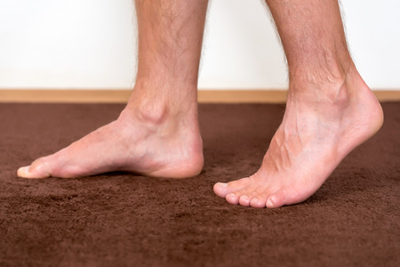 pies masculinos: Healthy male feet feeling comfortable at home. Foto de archivo
