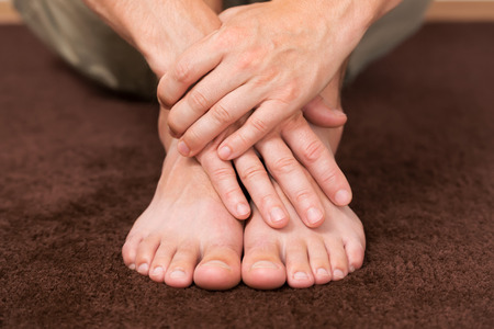 foot fungus: Male hands crossed over healthy resting feet.
