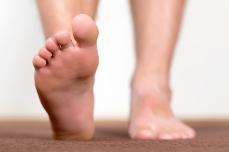 step well: Pair of clean male feet without any illness making a step.