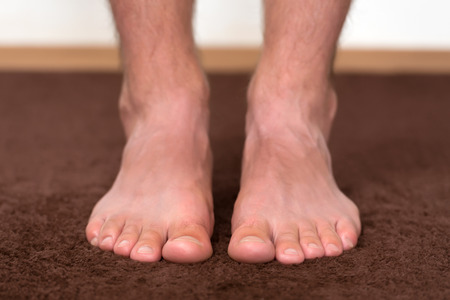 itchy: Itchy cold feet resting on the floor. Stock Photo