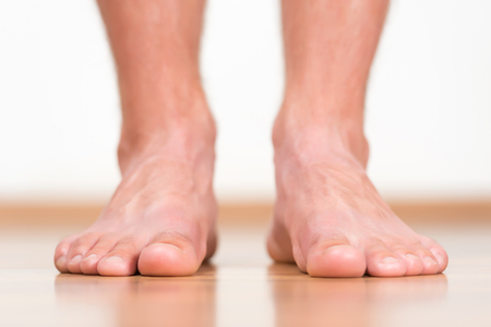 pies masculinos: Healthy male feet stepping over home-like background Foto de archivo