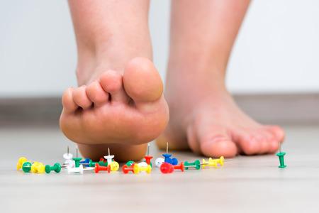 Vrouwelijke voet boven gekleurde punaise