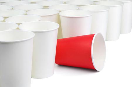 cup: Hay una vasos de papel vacíos blancos rojos y muchos aislados sobre fondo blanco. Las tazas blancas están en la diagonal de la imagen, la taza roja está entre ellos. Foto de archivo