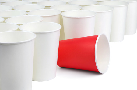 There is one red and many white empty paper cups isolated on white background. The white cups are on the diagonal of the image, the red cup is among them.