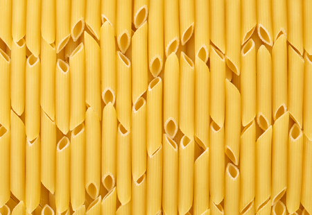 sorted: Italian uncooked pasta penne sorted vertically for background or texture. Stock Photo