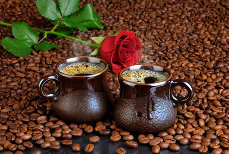 Two cups of black coffee with foam on the background from the fried coffee beans and a red rose. For cards for Valentine's Day.