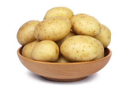 unpeeled: Raw unpeeled potatoes in a wooden bowl, isolated on white background.