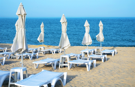Empty sun loungers and closed umbrellas on a deserted sea sandy beach on a clear day. Stock Photo