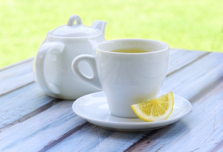 the brewer: Green tea in a white cup, a slice of lemon on a saucer and a teapot on a wooden table. Stock Photo