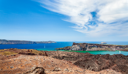Landscape of a group of volcanic islands of Santorini in the Aegean Sea on the background of blue sky with clouds. Greece.