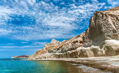 Views of the rocky coastline of the Greek island of Thira or Santorini and blue sky with spindrift clouds. Stock Photo