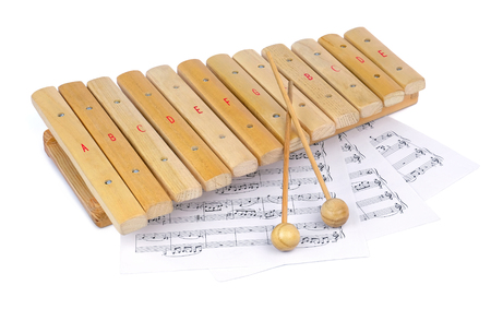 Small wooden xylophone and several sheets of paper with musical notes under it, isolated on a white background. Stock Photo