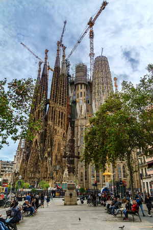 BARCELONA, SPAIN - OCTOBER 10, 2018: View of Sagrada Familia cathedral with construction cranes from pedestrian street.