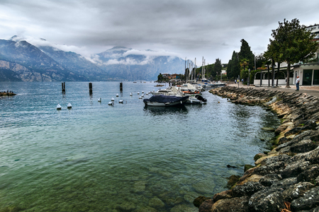 MALCESINE, ITALY - OCTOBER 1, 2018 : View of Lake Garda and the Alps, the seafront of the town on a cloudy autumn day. 報道画像