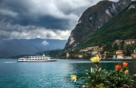 Menaggio, Lombardy, Italy - MAY 11, 2019: View of the famous Menaggio town and the ship on Como Lake, in the Alps before the storm, in inclement weather.