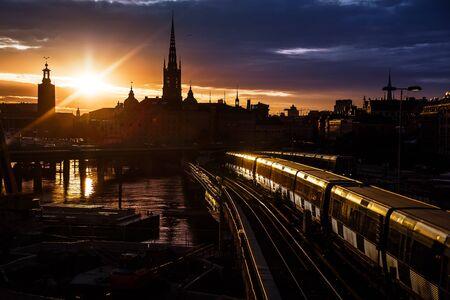 Toits de la ville de Stockholm. La vue sur la vieille ville, Gamla Stan et l'église Riddarholmen depuis le pont central Centralbron avec des trains locaux dessus pendant le coucher du soleil. Suède. Banque d'images
