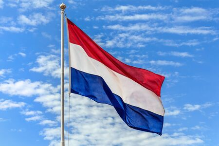 The national flags of the Netherlands flag on the background of blue sky with clouds.