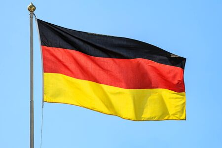 The national flags of Germany on the background of clear blue sky.