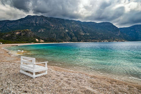 Empty Oludeniz beach out of season on the background of the mountains in pre-thunderstorm weather. Mugla, Turkey.