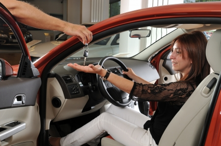 Happy red head woman buying a new car