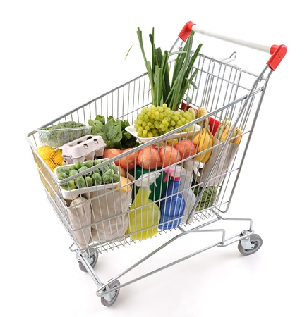 Shopping trolley full of grocery isolated on white  photo