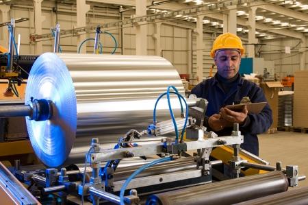 bobina: Trabajador de una fábrica con la bobina de aluminio de la máquina de procesamiento de