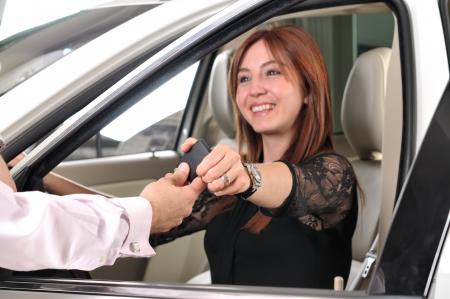 幸せの赤い頭の顧客に新しい車のキーを与えることの車のディーラー