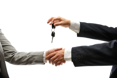 Car dealer giving keys of a new car to female buyer Stock Photo