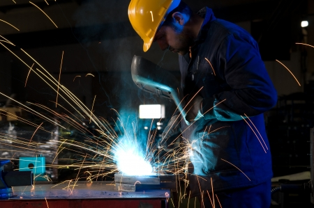 skilled: Worker making sparks while welding steel isolated   Stock Photo