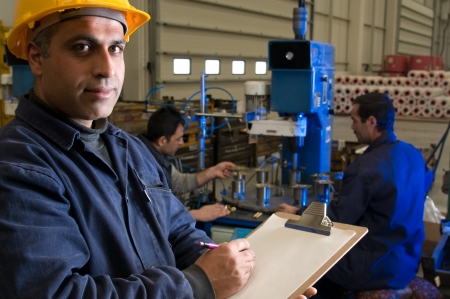 Inspector controlling workers at wood factory Stock Photo - 14287468