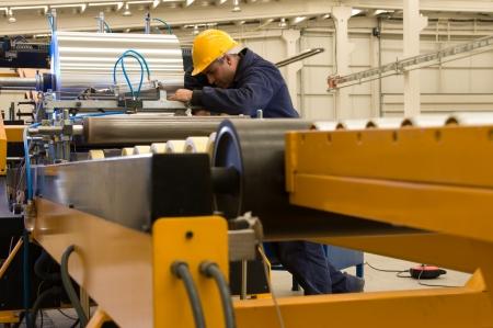 Factory worker processing roll of steel sheet