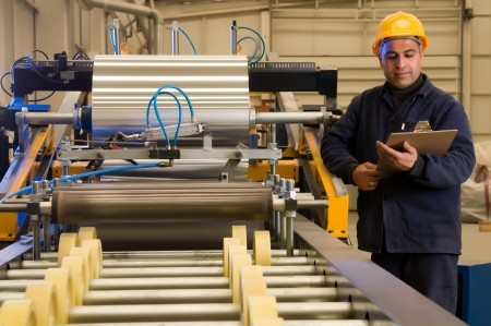 heavy industry: Factory worker processing roll of steel sheet Stock Photo
