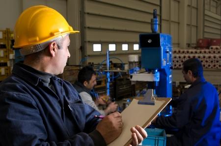 Inspecteur het regelen van de werknemers op het hout in de fabriek