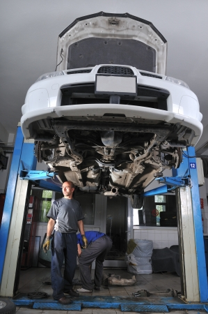 Auto mechanic working under the car - a series of MECHANIC related images photo