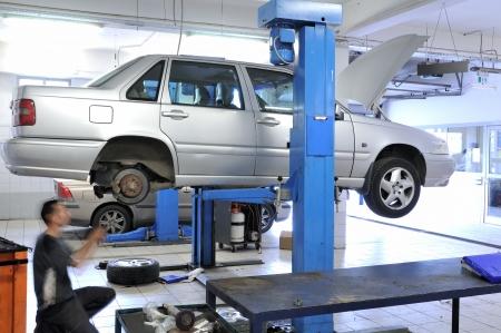 ブレーキをチェックする車の機械工のホイール ナットの取り外し