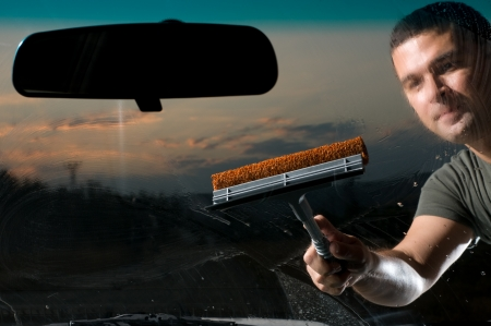 Adult man washing dirty windshield of his car photo