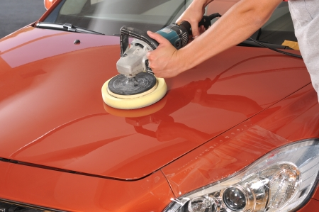 polish: Car care with power buffer machine at service station