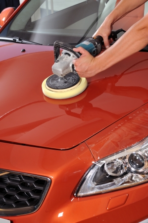 Worker waxing orange car by polishing machine  Stock Photo