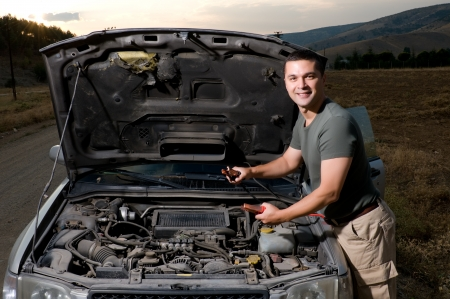 dirty car: Adult man using jumper cables to start a car battery Stock Photo